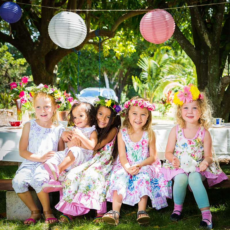 Five girls, wearing haku lei flower head crowns, are dressed in light pink, green and yellow pastel floral Twirling Dresses made by Cool Blue Maui, sit and smile at an outside tea party.