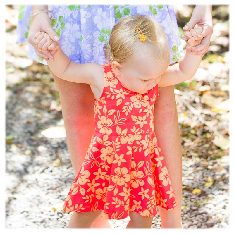 12 month old baby girl with blond hair is wearing a bright two-tone orange Hawaiian floral Holoholo Dress by Baby Blue by Cool Blue Maui who makes island inspired girls' dresses.