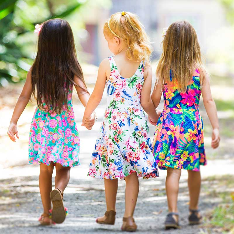 The backs of three girls in colorful island inspired girls' dresses that are Hawaiian floral Holoholo Dresses by Baby Blue Cool Blue Maui are holding hands, walking down a gravel road in the sun.
