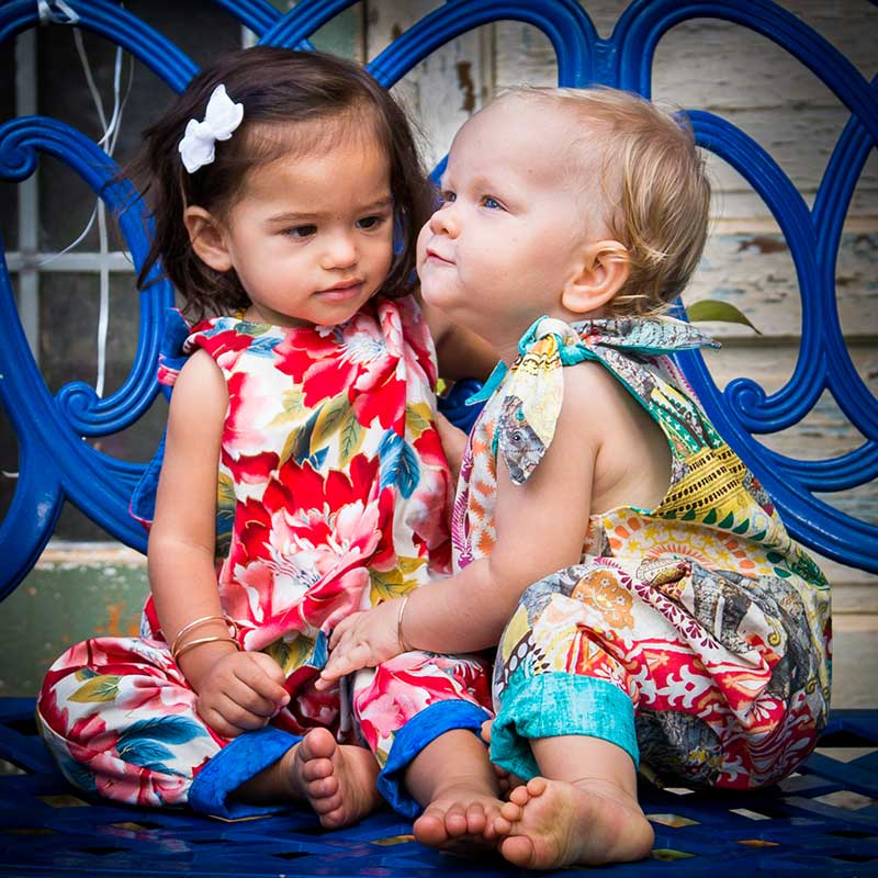 Two baby girls wearing red flowers and elephant printed rompers made by Baby Blue by Cool Blue Maui who creates inspired girls' dresses and rompers for toddlers sit together on a blue bench.