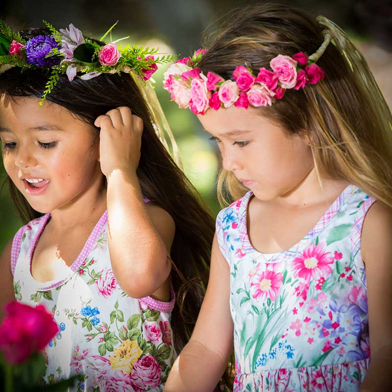 Close up of two your girls with pink rose flower head leis are wearing island inspired girls' dresses that are pastel flower printed Baby Blue by Cool Blue Maui Twirling Dresses.