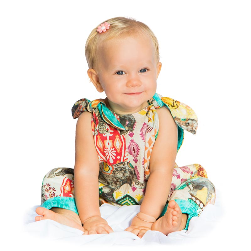 A 12 month blond baby girl sits against a white backdrop as she smiles while wearing an Elephant Walk Romper made by Baby Blue.