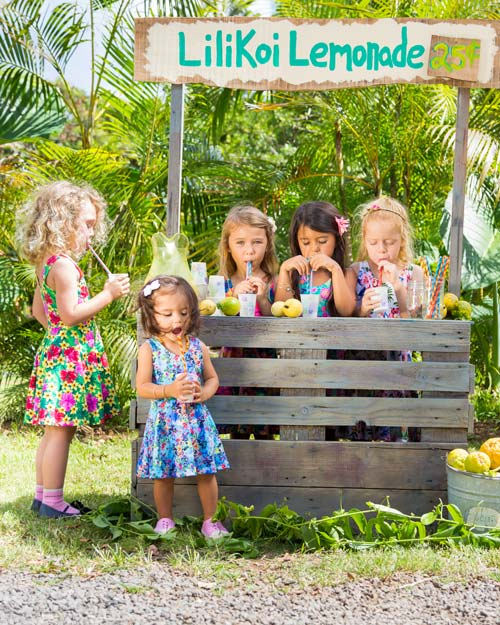 5 girls wearing Hawaiian print Holoholo Dresses all drink lemonade from straws at a rustic Maui style Lilikoi Lemonade stand.