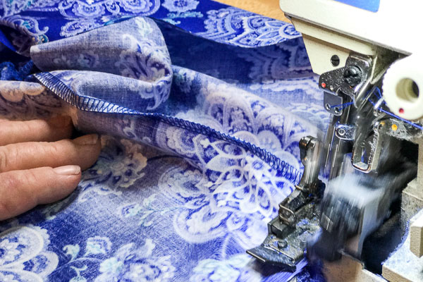 Close up picture of Pamela Winans of Cool Blue Maui using a sewing machine to makes a blue Mandala Twirl Dress.