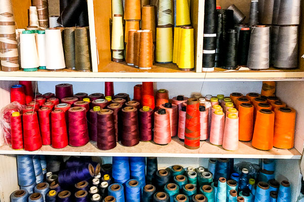 Red, blue, orange, yellow, gold, pink, silver, black and white rolls of thread on a shelf at Cool Blue Maui.