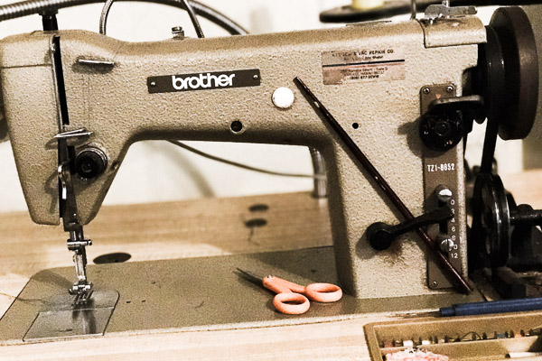 Industrial Brother sewing machine with a pair of orange scissors at Cool Blue Maui shop.