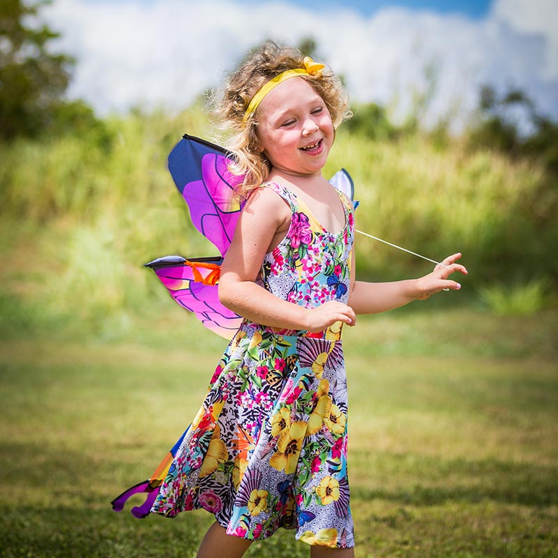 A girl in a yellow, blue, and pink floral Holoholo Dress by Cool Blue Maui smiles while playing with a dragonfly kite in the sunshine.