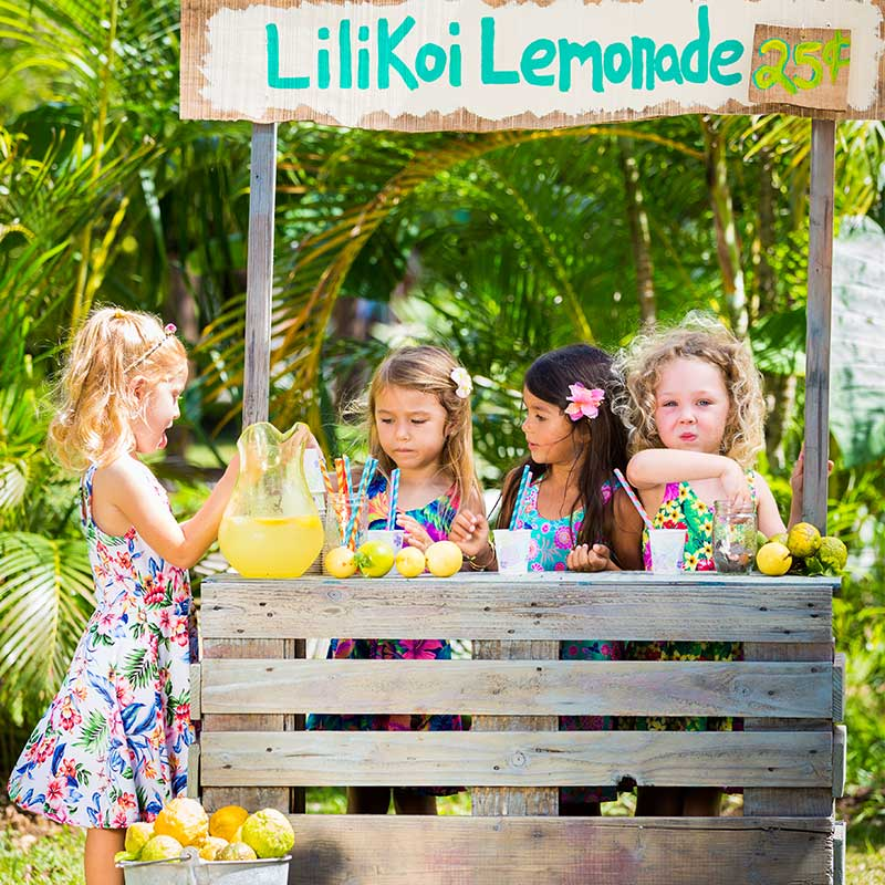Four girls dressed in Hawaiian floral Holoholo Dresses by Baby Blue of Cool Blue Maui serve lilikoi lemonade at their rustic stand made of palettes.