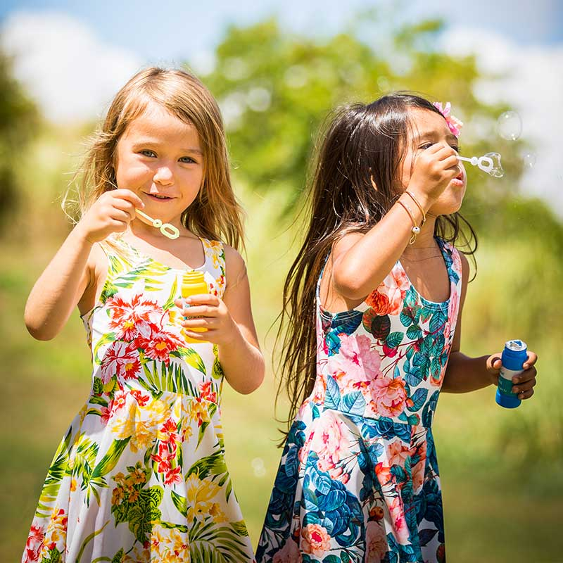 Two girls blow bubbles while wearing brightly colored pink, green, red and yellow floral Holoholo Dresses.