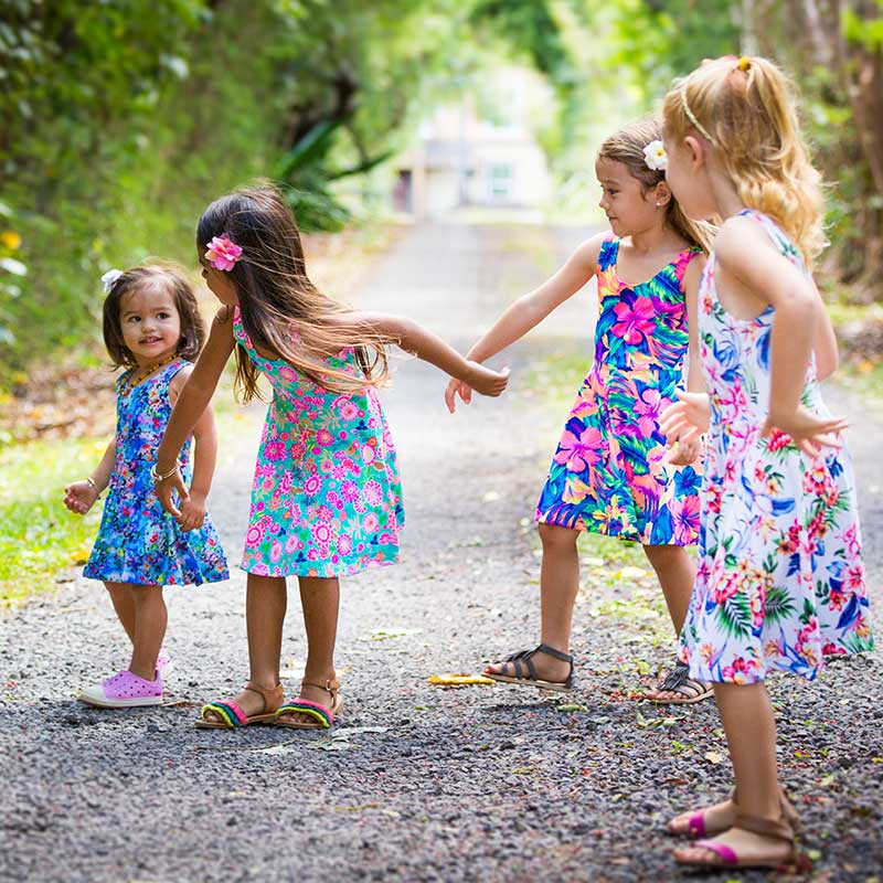 Four girls hold hands while adventuring down a gravel road in Hawaiian print Holoholo Dresses made by Cool Blue Maui.