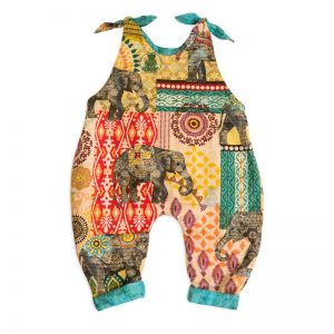 The front side view of Baby Blue by Cool Blue Maui's Elephant Walk Romper which has large gray elephants walking among multi color batik motifs and a jade green scratch fabric cuff.