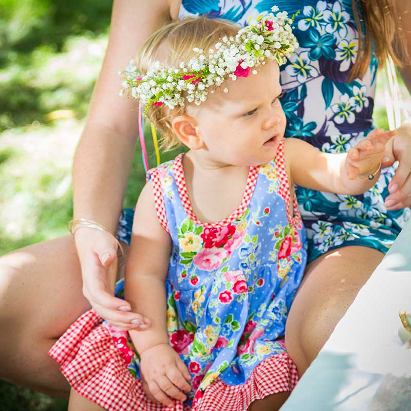 A baby girl with flowers in her hair is wearing a Baby Blue Twirling dress that has a blue background with red, yellow, and pink flowers on it.
