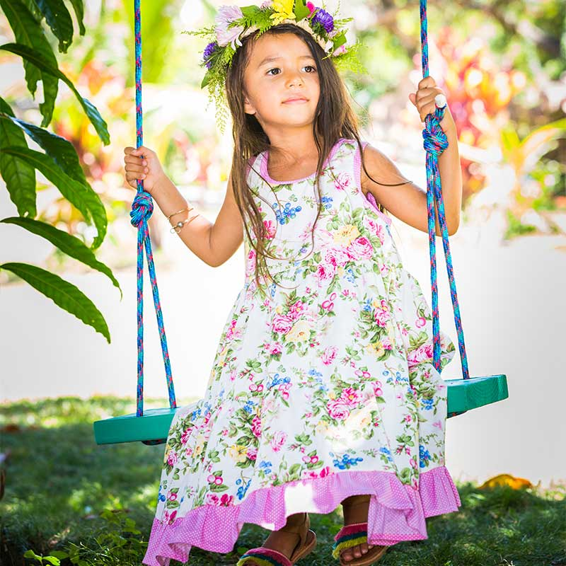 A young girl in a swing has yellow and pink flowers in her hair and is wearing a light colored floral pink and yellow long Twirling Dress.