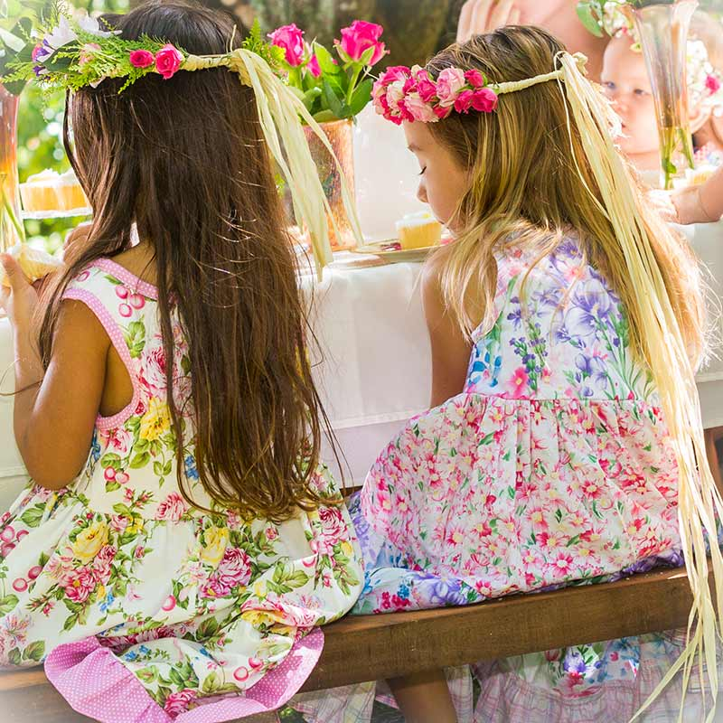 Two girls wearing floral pink, purple and yellow Twirling dresses sit on a bench at an outside magical tea party.