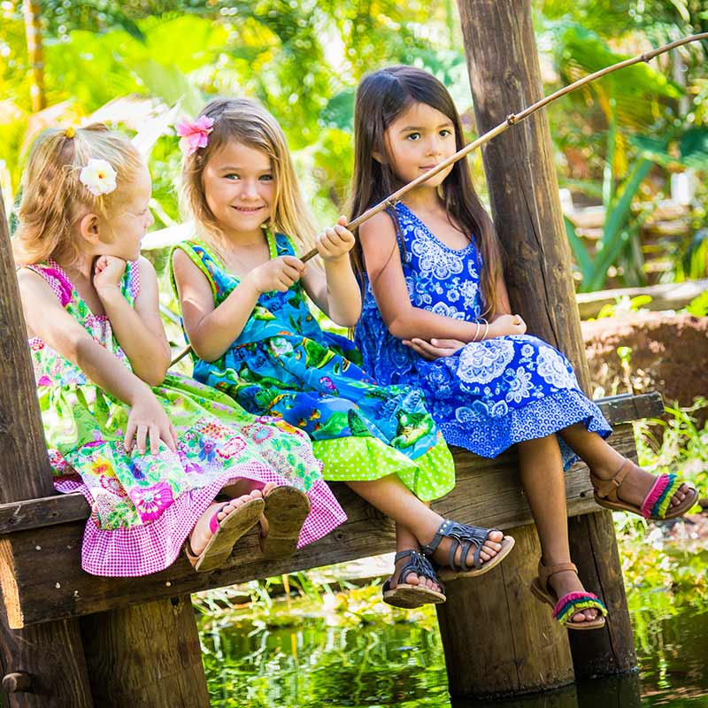 Three girls dressed in green, blue and pink Baby Blue by Cool Blue Maui Twirling Dresses are sitting smiling on a wooden dock with a bamboo fishing Pole.