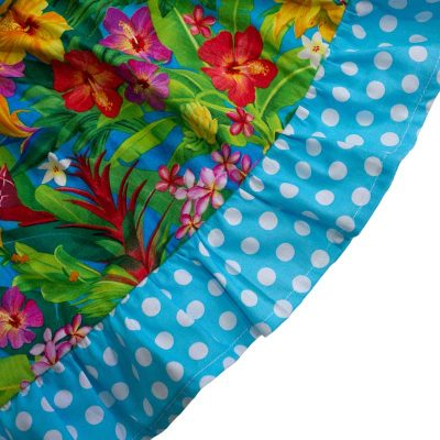 Close up fabric view of Baby Blue by Cool Blue Maui's Aloha Minnie Twirling Dress which has bright yellow, red, purple, and orange assorted Hawaiian tropical flowers and a blue with white polkadot hem.