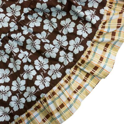 Close up fabric view of the Baby Blue Aloha Plaid Twirling Dress by Cool Blue Maui which has chocolate brown background with light blue hibiscus flowers and a blue, brown, yellow, orange plaid hem.