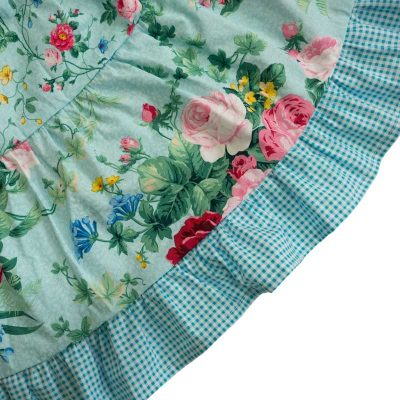 Close up fabric view of the Baby Blue English Garden Aqua Twirling Dress by Cool Blue Maui which has an aqua background with large pink and red cabbage rose bouquets mixed with smaller rose print and a aqua gingham trim and ruffle.