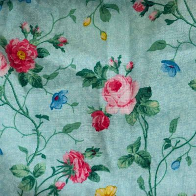 Close up fabric view of the Baby Blue English Garden Aqua Twirling Dress by Cool Blue Maui which has an aqua background with small pink and red roses.