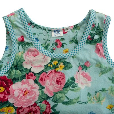 Close up view of the tank-top style top of a Baby Blue by Cool Blue Maui's English Garden Aqua Dress in a size 5 which has an aqua background with large pink and red cabbage rose bouquets mixed with smaller rose print and a aqua gingham trim.