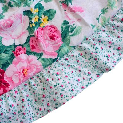 Close up fabric view of Baby Blue by Cool Blue Maui's English Garden White Twirling Dress which has a white floral background with small pink roses, green leaves and large red and pink cabbage roses and a pink baby flower hem.