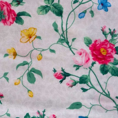 Close up fabric view of Baby Blue by Cool Blue Maui's English Garden White Twirling Dress which has a white floral background with small pink roses, yellow flowers, green leaves and large red and pink cabbage roses.