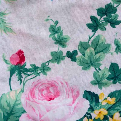 Close up fabric view of Baby Blue by Cool Blue Maui's English Garden White Twirling Dress which has a white floral background with green leaves and large red and pink cabbage roses.