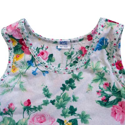Close up view of the tank-top style top of a Baby Blue by Cool Blue Maui's English Garden White Dress in a size 5 which has a white floral background with small pink roses, green leaves and large red and pink cabbage roses and a pink baby flower hem.