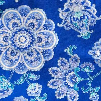 Close up view of the blue and silver flower shaped mandala design fabric of a Baby Blue Mandala Twirling Dress by Cool Blue Maui.