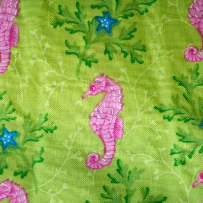 Close up fabric view of Baby Blue by Cool Blue Maui's Seahorse Garden Twirling Dress which has bright pink seahorses and blue stars on a lime green background.