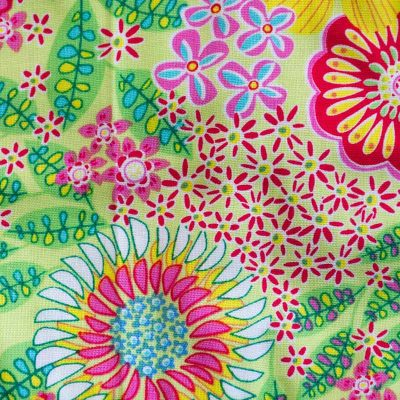 Close up fabric view of Baby Blue by Cool Blue Maui's Seahorse Garden Twirling Dress which has bright pink, red, blue and yellow flowers on lime green background.