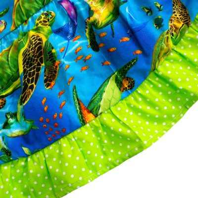 Close up fabric view of Baby Blue by Cool Blue Maui's Turtle Town Twirling Dress which has a bright blue ocean background with swimming green sea turtles and a bright green polkadot hem.
