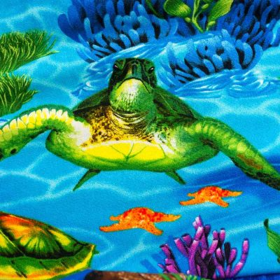 Close up fabric view of Baby Blue by Cool Blue Maui's Turtle Town Twirling Dress which has a bright blue ocean background with swimming green sea turtles.