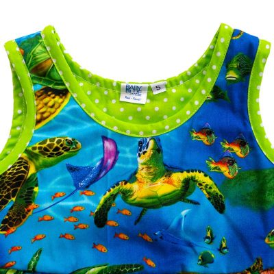 Close up view of the tank-top style top of a Baby Blue by Cool Blue Maui's Turtle Town Twirling Dress in a size 5 which has a bright blue ocean background with swimming green sea turtles and a bright green polkadot hem.