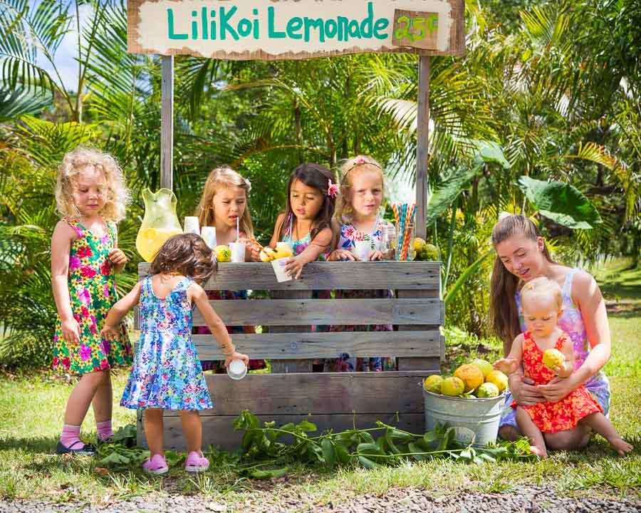 Girls wearing holoholo swimsuit sundresses at Lilikoi Lemonade stand drinking lemonade and laughing in the sun.