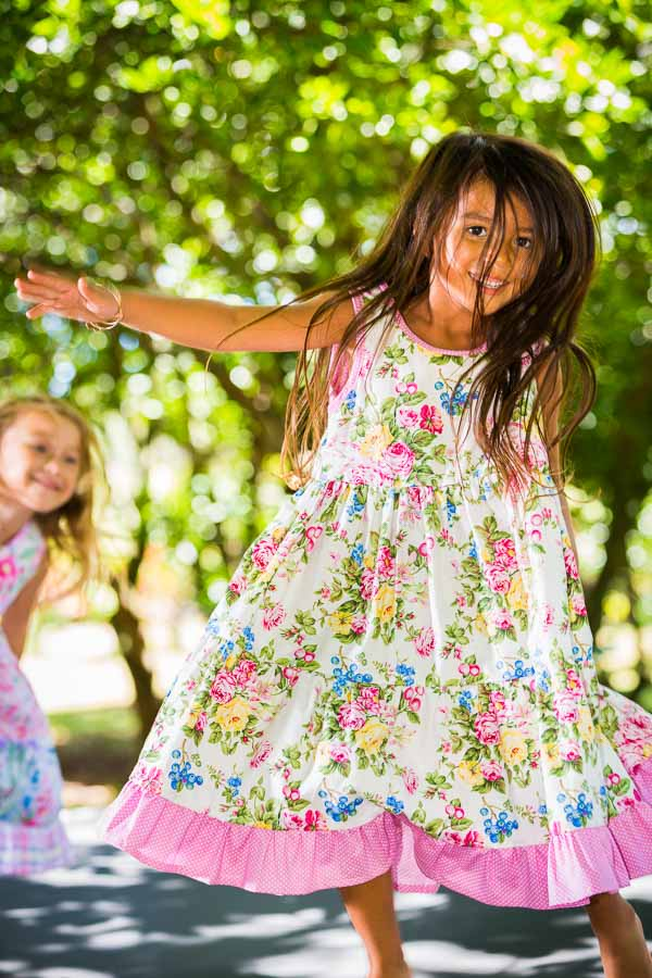 Happy girl jumping on trampoline in her girl's party dress made in Maui.