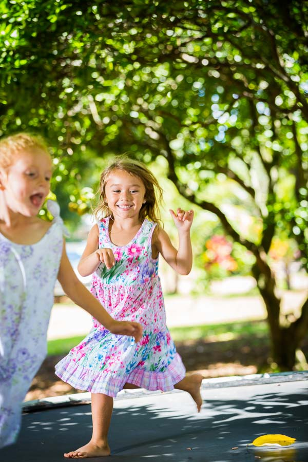 Kids playing on trampoline smiling in their girls party twirl dress and floral romper.