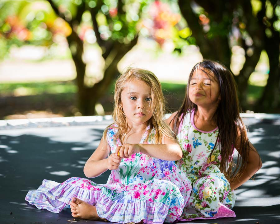 Cute girls sitting on trampoline in their floral twirl party dresses after a fun tea party.