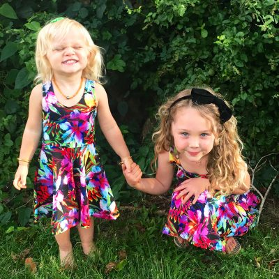 Smiling girls holding hands dressed in bright Hawaiian floral Hug a Rainbow holoholo girls sundresses.
