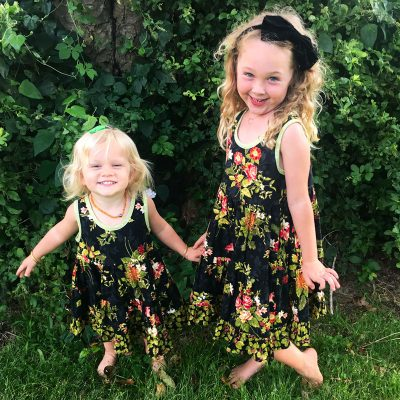 Girls smiling and holding hands wearing Holiday Bouquet Twirl Dresses.