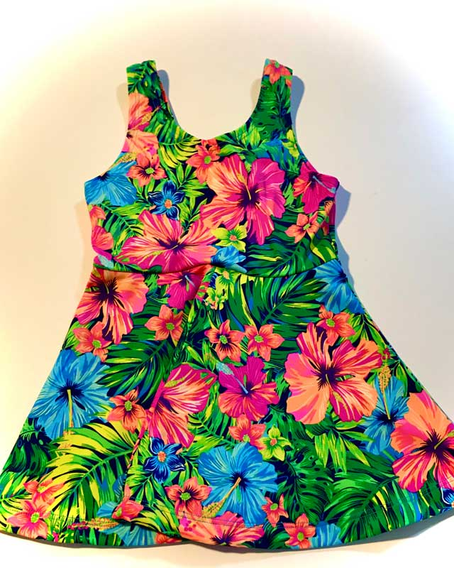 Girls swimsuit sundress with bright hibiscus pink flowers and green and blue palm background featured at the Hawaiian Airlines Made in Maui County Festival.