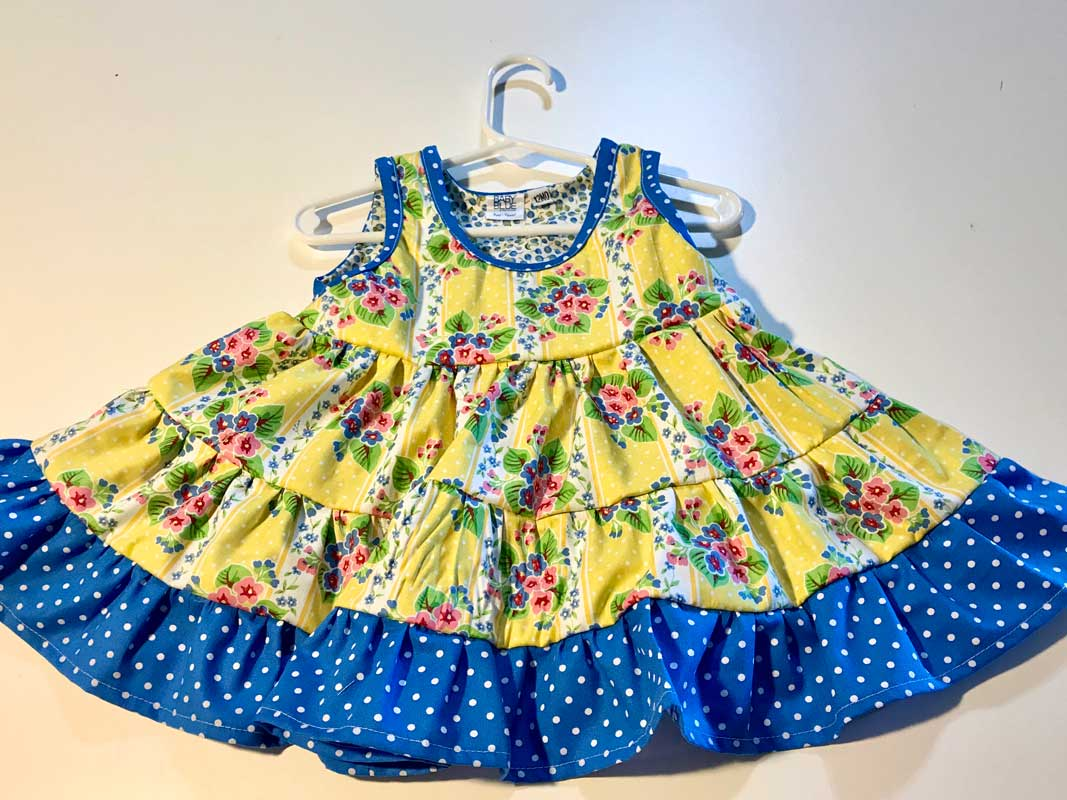 Girls Twirl Dress has yellow background with pink and blue floral roses and a blue with white polka dot trim featured at the Hawaiian Airlines Made in Maui County Festival.